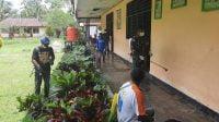 """Brantas Covid-19 di Perbatasan, Satgas Pamtas RI-PNG Yonif Mekanis 512/QY """"Hujani' Kampung Mannem dengan Disinfektan"""